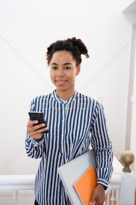 Young woman with dark hair holding a cell phone