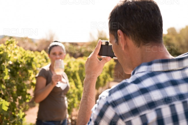 Man taking a photo of a woman in a vineyard