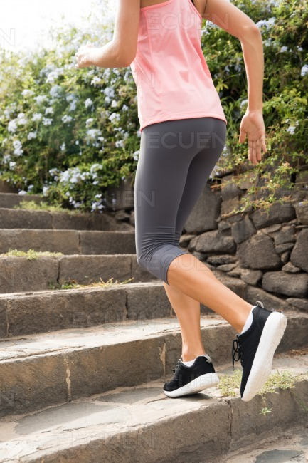 Woman running up grey stone steps