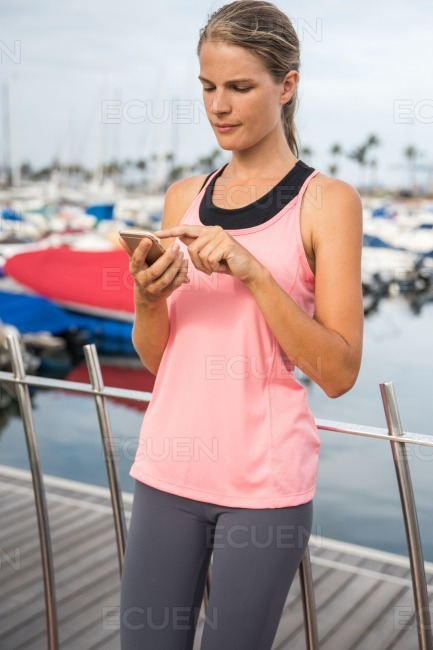 Young female runner checking her phone