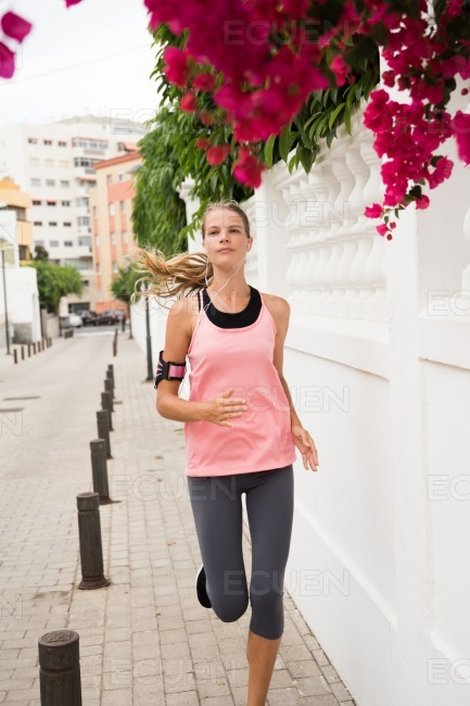 Young girl jogging down the road past pink flowers stock photo
