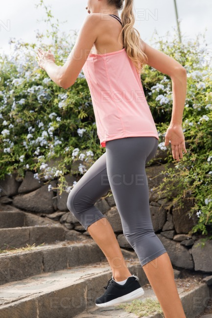 Young girl running up grey stone steps stock photo