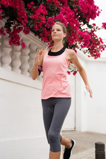 Young woman running past pink flowers