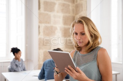 Blonde woman holding a tablet pc and typing