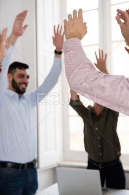 Corporate group celebrating with raised hands