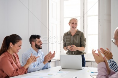 Group of office colleagues laughing and clapping