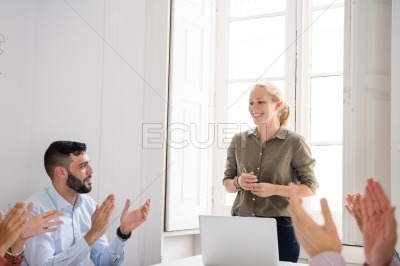 People clapping after a presentation in a meeting