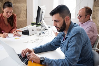 Three work colleagues sitting at a desk working