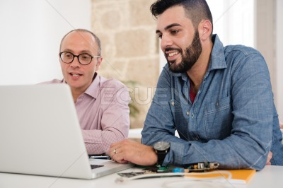Two men looking at a laptop whilst talking