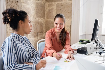 Two women in an office talking and laughing
