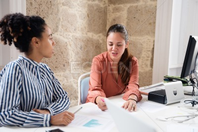 Two women looking at papers in an office
