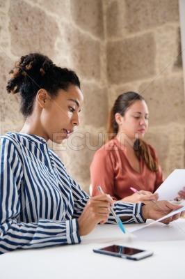 Two women reading from papers they are holding
