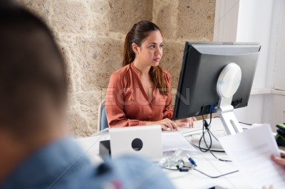 Woman sits at a desk and looks at a computer