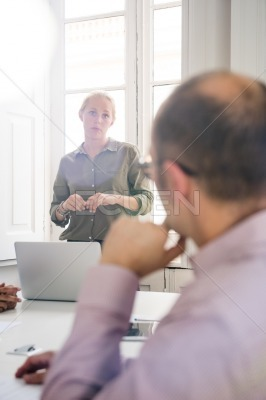 Woman with a green shirt is talking to a man