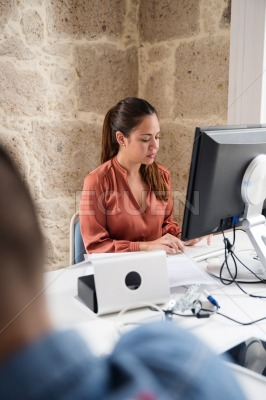 Woman works at a desk top computer