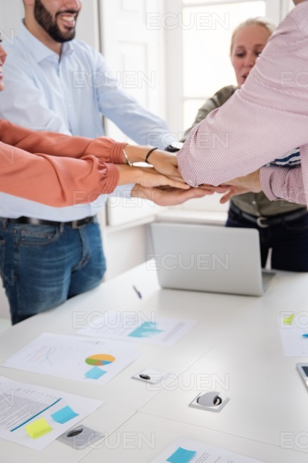 Colleagues celebrating in an office holding hands