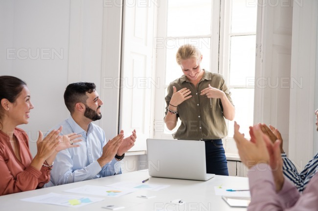 Woman being applauded at work after a presentation
