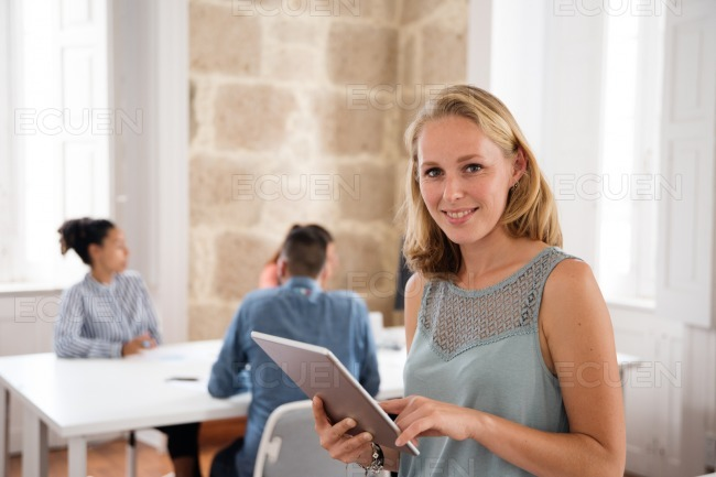 Woman smiles at the camera as she holds a pc table stock photo