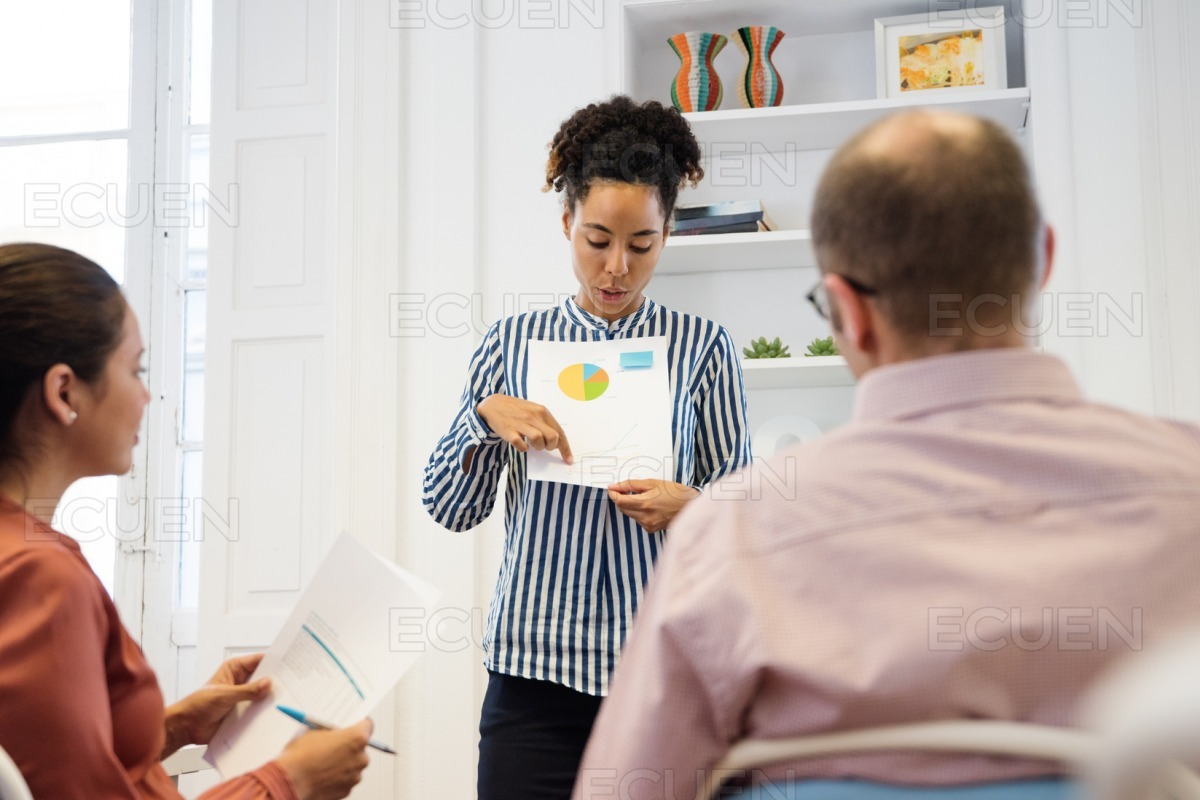 Woman giving a presentation to colleagues stock photo