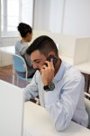 Man at a desk talking on a cell phone