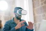 Man testing virtual reality glasses with hands up