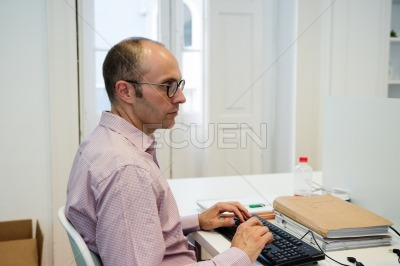 Balding man in a pink shirt typing on a keyboard