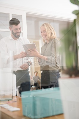 Man and woman laughing as she holds a pc tablet