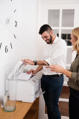 Man and woman laughing over a photo copier
