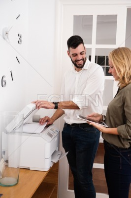 Man at a photo copier and woman holding tablet pc