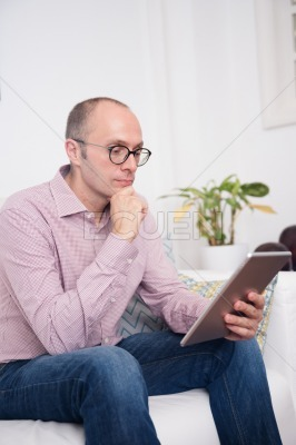 Man leans forward holding a pc tablet