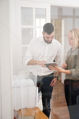Man pointing to a pc tablet that a woman holds