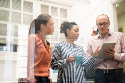 Three business team members holding a pc tablet
