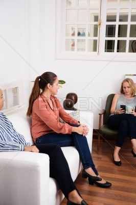Three woman sitting in a lounging area