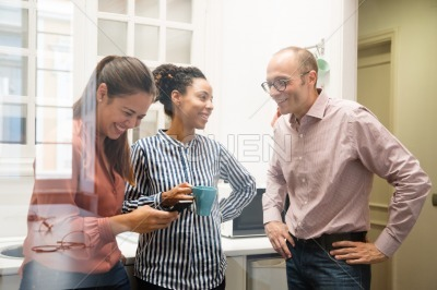 Three work colleagues laughing in a kitchen