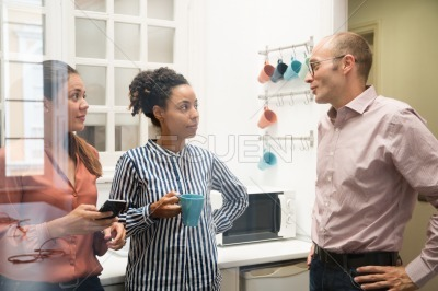 Three work colleagues talk in an office kitchen