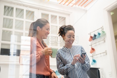 Two business women laughing in an office kitchen