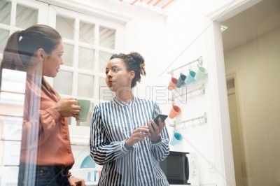 Two business women talking in an office kitchen