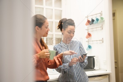 Two woman pointing at a cell phone in a kitchen