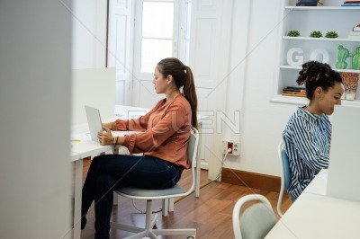 Two women sitting in an office working on computer