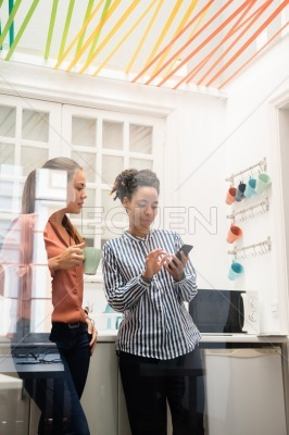 Two women standing in a kitchen looking at a cell
