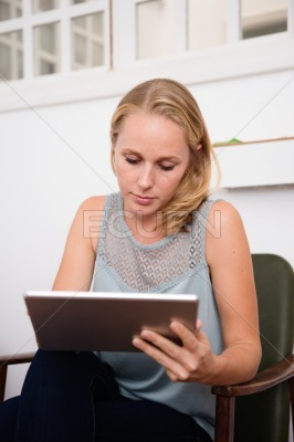 Woman looking at tablet while sitting in a chair