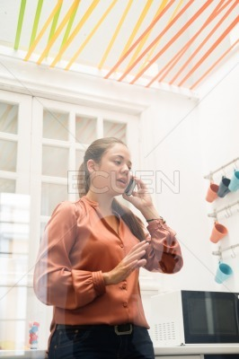 Woman standing in kitchen talking on a cell phone