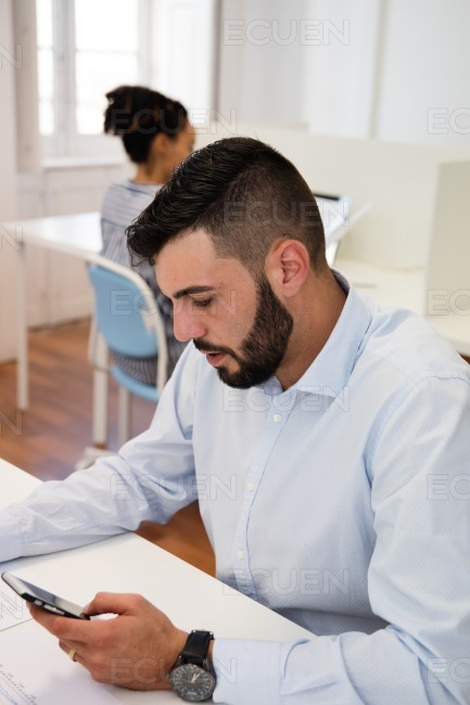 Man at a desk looking down at cell phone