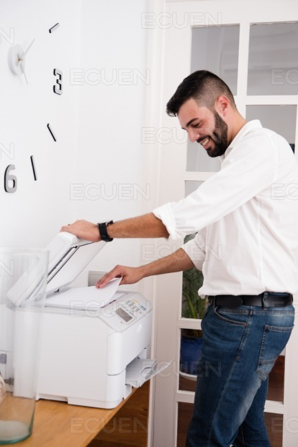 Man smiling as he uses a photo copier stock photo