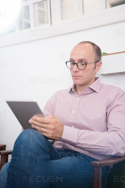 Man testing from a pc tablet as he sit in a chair