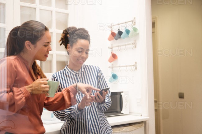 Two business women pointing at a phone in a kitche