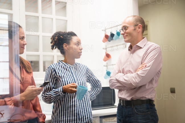Two women and a man in an office kitchen