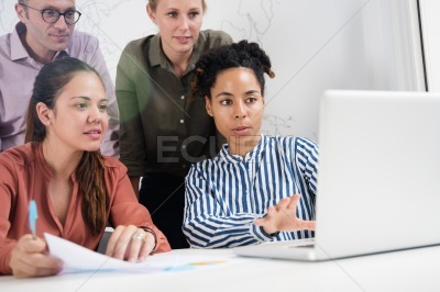 Business team looking at a laptop and gesturing