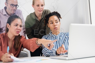 Business team looking at a laptop and pointing