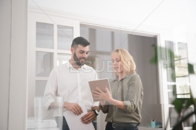 Man and woman in an office looking at a pc tablet